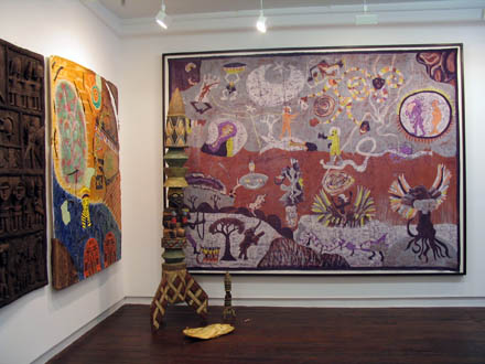 Picture of installation of paintings and sculpture depicting space themes merging contemporary and traditional Burkina Faso art styles