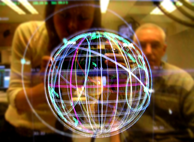 Bright projection of a globe apparently onto a transparent screen or floating, behind which a man and woman are seen