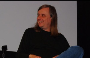 Photo of Steve Kurtz in panel discussion smiling in black jumper and blue jeans