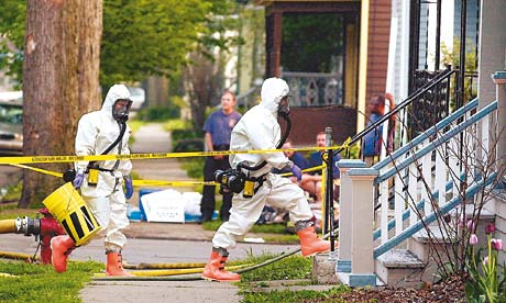 Men in white hazard suits enter a house marked of by yellow warning tape
