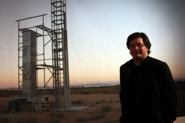A man stands in front of a launch site in the desert