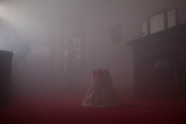 a smoke-filled domestic living room with a model volcano in the centre