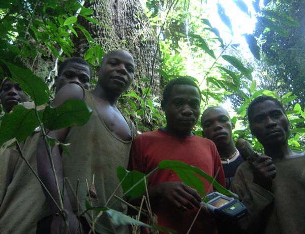 A group of young Congalese men in a forest, one with a handheld device