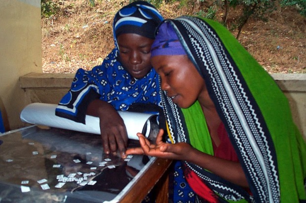 Two young Tanzanian women work on a map