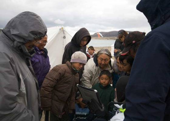 A group of Inuit people gather around a portable device