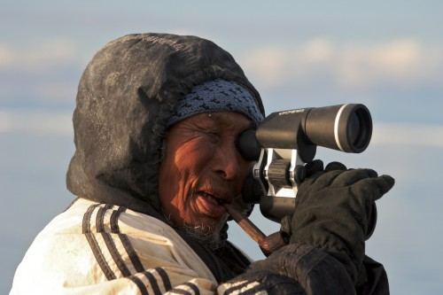 Inuit man using electronic telescope