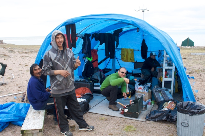 Two Inuit and two other men in a makeshift blue tent