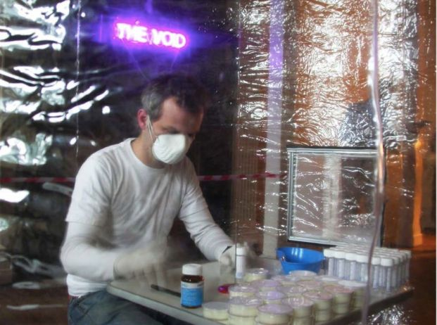 An artist in a respiratory air mask sits in a plastic tent. Test tubes and bottles on a table in front of him.