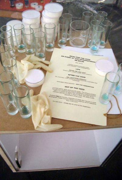 Glasses and dishes on a table, rubber gloves, a sheet of paper with 'Menu for the Void'