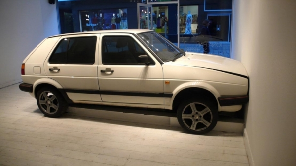 A small white car in a gallery, its front end against the wall, car bonnet beginning to buckle