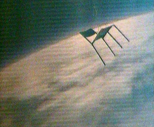 A chair floats above the Earth against the blackness of space