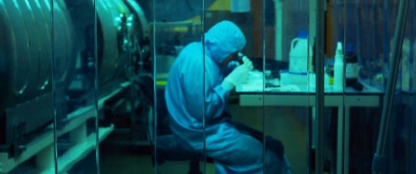 Image of scientist in clean room looking down microscope