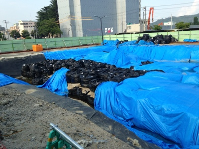 Numerous black bags containing soil with blue covering in large hole in central city location