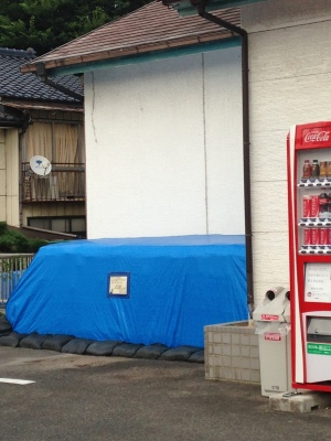 Blue covered pile outside shop with vending machine next to it
