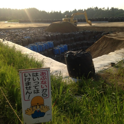 Vast hole in the ground containing large black and blue plastic bags. Sign - picture of worker with hands outstretched in warning and Japanese writing