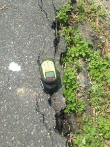 Geiger counter placed on a crack in the road
