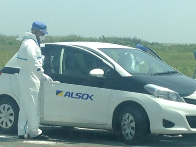 Men in white overalls and face masks get into a white car