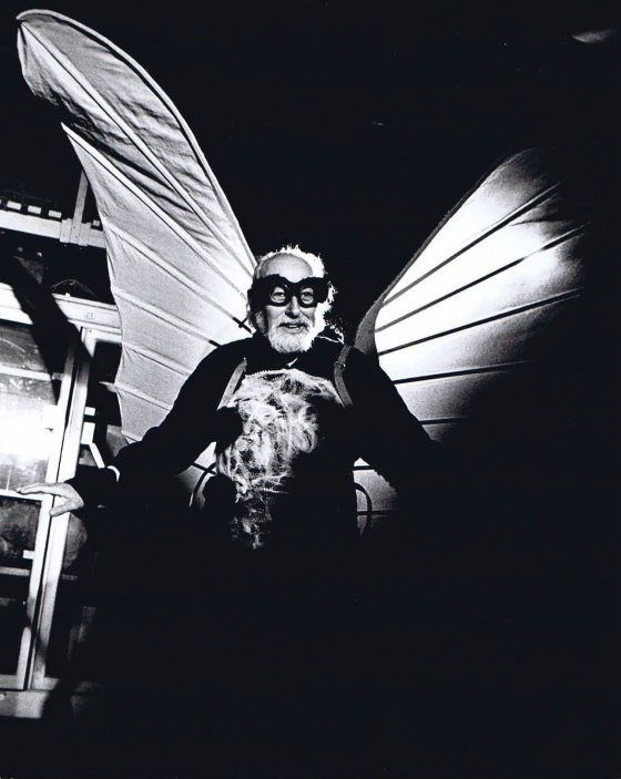 B&W photo. Man dressed as giant butterfly