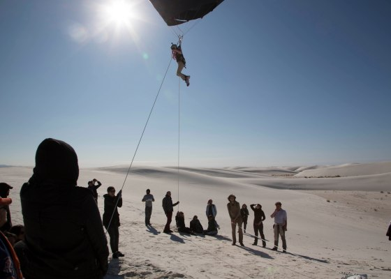 black balloon, person suspended, white desert, blue sky