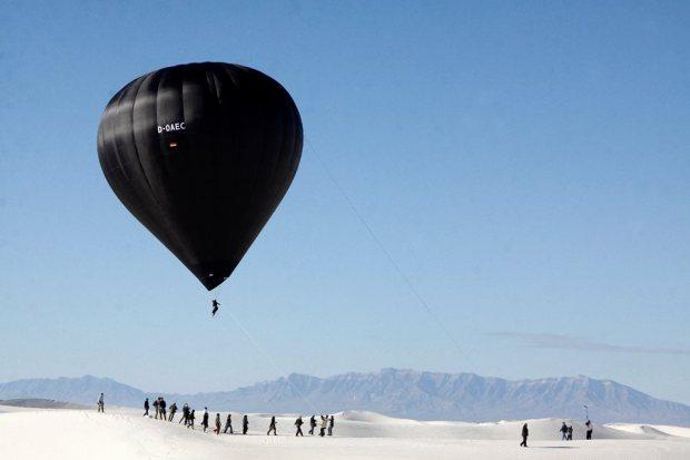 black balloon, person suspended, white desert, blue sky