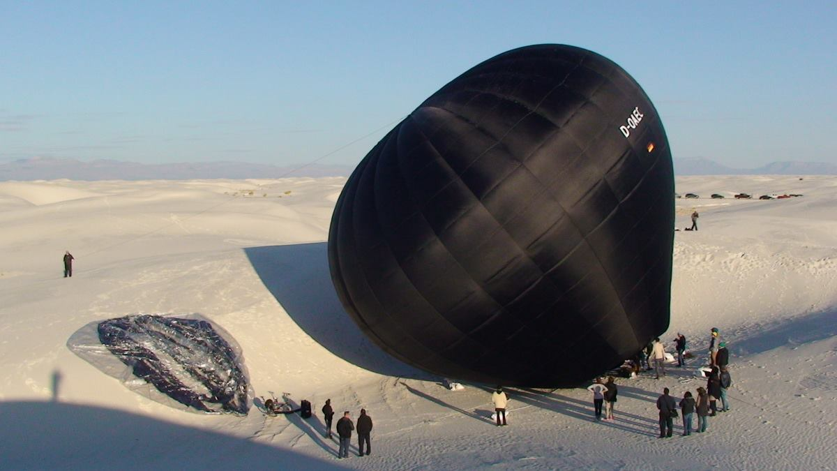 Black balloon lying in desert
