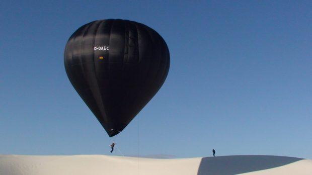 Black balloon, white desert, blue sky, person suspended
