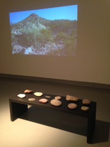 Engraved rocks in front of projected film with mountain